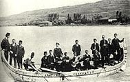 Pontian men wearing western suits in a canoe, Black Sea. Some wear fezes or carry instruments.
