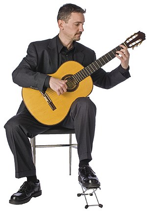Classical guitar technique - A guitarist demonstrating traditional classical guitar posture