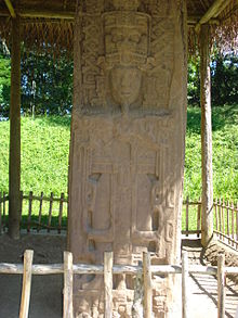A stela with the prominent sculpture of a king surrounded by elaborate decoration. The monument is covered by a thatched roof supported on wooden poles.