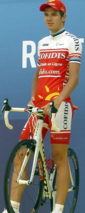 A man in his early twenties wearing a red and white cycling jersey with black trim, standing atop a stationary bicycle.