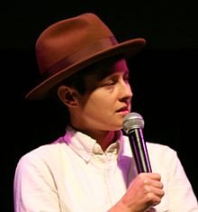 Rhea Butcher speaking into a microphone. Butcher is Caucasian, wearing a brown hat and white shirt, and facing to the right.