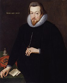 "A portrait of Robert Cecil, who is standing at a table wearing black robes. He has neck length brown hair, and a pointed goatee. He has gold lettering behind him, which reads ""sero, sed serio."""