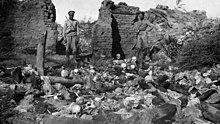 Photographie de deux soldats russes dans un village en ruine regardant des restes squelettiques