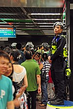 A Singapore Police Force officer from the Public Transport Security Command surveys the high traffic volume in the immediate hours after the 2010 new year celebrations at City Hall MRT Station. The officer dons a new light-grey-coloured beret which was introduced on 30 December 2009 and which replaces the dark blue one.