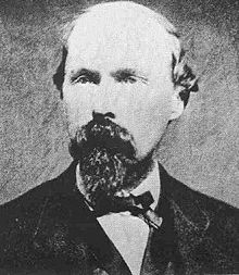 Black and white photograph of a balding man with a beard