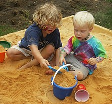 Young boy and girl filling a pail in a sandbox