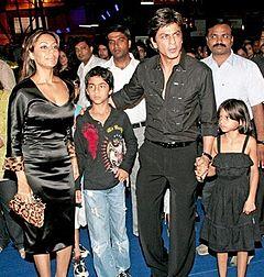 Shahrukh Khan debout, avec un enfant de chaque côté de lui, et une femme.