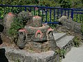 Shiva Lingam in the foreground and Nandi, the bull, the carrier of Shiva behind it. This is in Pokhara at Davis Falls.jpg