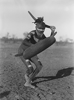 A Luritja man demonstrating his method of attack with a large curved boomerang under cover of a thin shield (1920) Showing method of attack with boomerang - NMA-15147.jpg