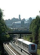 Um trem de dois carros segue os trilhos sob uma ponte.  Ao fundo, pode-se ver um estádio esportivo abobadado e edifícios altos.