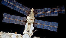 A view of the Spektr module with the blackness of space behind. In view are the module's four golden solar arrays, in addition to the cylindrical module itself, covered in white insulation and with a cone at the distal end of the module. Two of the arrays project from this cone, and two project from the distal end of the cylinder.