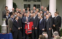 President George W. Bush receives the New Jersey Devils players in the White House doors. Bush holds a Devils jersey with the name Bush and the number 1. To the left of the crowd, the Stanley Cup sits on a table.