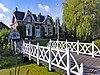 Woonhuis in overgangsarchitectuur met hek en brugbalustrade