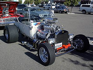 Hot rod - T-bucket with early hemi, but aluminum radiator (rather than brass), rectangular headlights, and five-spokes (rather than motorcycle wheels) mark this as a later incarnation.