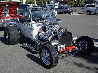 Hot rod - T-bucket with early hemi, but aluminum radiator (rather than brass), rectangular headlights, and five-spokes (rather than motorcycle wheels) mark this as a later incarnation