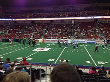 Players setting up on an arena football field