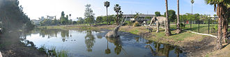 Hancock Park - Panorama of a tar pit pond with sculptures of prehistoric mammals in Hancock Park