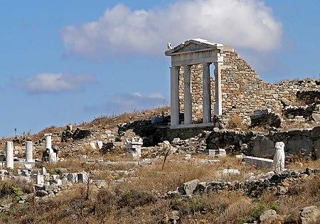 A hillside littered with broken columns. An intact set of columns, supporting a pediment, still stand.