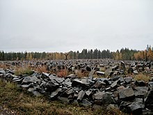 Thousands of scattered rocks litter the landscape. In the distance, leaves of trees are slowly turning yellow. It is the site of a Winter War monument at Suomussalmi, Finland, containing a rock for every soldier that died at the Battle of Suomussalmi: 750 Finnish and estimated 24,000 Soviet.