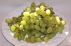 On a white plate rests a cluster of golden, green-colored Thompson Seedless grapes.