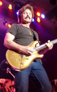 Johnston playing a Paul Reed Smith Artist's Gold Top while wearing a black t-shirt and jeans, in front of colorful stage lights