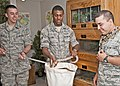 U.S. Air Force Airman 1st Class Allen Airoldi holds a burlap sack so Airman 1st Class Lennell Day can safely put a Great Plains Rat Snake into it for safe transport at Sheppard Air Force Base, Texas, July 25 110725-F-NS900-003.jpg