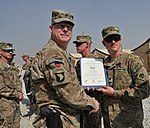 U.S. Army Brig. Gen. Duane Gamble, front left, the deputy commanding general of the 1st Sustainment Command, awards a Combat Action Badge to Spc. Joseph J. Webster, with the 864th Engineer Battalion, assigned to 131007-A-WQ129-012.jpg