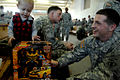 U.S. Army Spc. Robert Featherstone and his son donate a toy during Operation Toy Drop at Fort Bragg.jpg