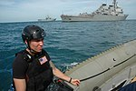 U.S. Navy Gunner's Mate 2nd Class Martin Vasquez, a member of the visit, board, search and seizure team assigned to the guided missile destroyer USS Curtis Wilbur (DDG 54), foreground, returns to the ship 130610-N-AX577-166.jpg