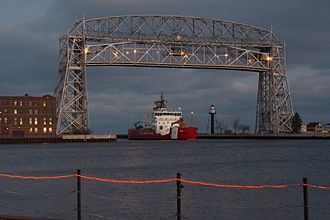 Duluth Ship Canal - USCGC Mackinaw entering the harbor from the canal, beneath the Aerial Lift Bridge. The rear range light can be seen behind it.