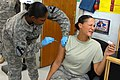 US Army 52429 BAGHDAD - Staff Sgt. Renatta Draper (right), from Bemidji, Minn., winces as Sgt. Danielle Dubose, a health care non-commissioned officer, from Detroit, gives her the annual flu shot at the Battalion A.jpg