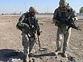 US Army 52926 BAGHDAD- Spc. Mario Macias (left), from Fort Worth, Texas, uses a metal detector to search for improvised explosive devices along the Baghdad-Diyala highway with help from Spc. Nathan Huhn, from Roots.jpg