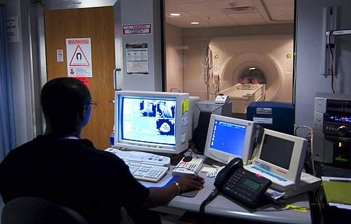 US Navy 030819-N-9593R-228 Civilian technician, Jose Araujo watches as a patient goes through a Magnetic Resonance Imaging, (MRI) machine