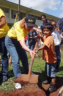 US Navy 040422-N-3019M-003 Master-at-Arms 3rd Class Angela Jeffery, assigned to Pearl Harbor Security Detachment, helps a child from Webling Elementary School dig a hole for a Ku Kui tree in honor of Earth Day.jpg