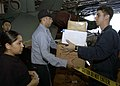 US Navy 041209-N-9079D-026 Postal Clerk 3rd Class Brian Pena, center, distributes mail to Sailors in the hangar bay aboard the Nimitz-class aircraft carrier USS Abraham Lincoln (CVN 72).jpg