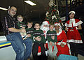 US Navy 071205-N-1512O-064 Electronics Technician 1st Class James Carey, assigned to the multi-purpose amphibious assault ship USS Bataan (LHD 5), and his sons, enjoy a visit with Santa and Mrs. Claus at the command's children'.jpg
