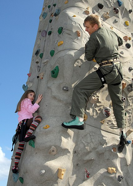 US Navy 090403-N-9860Y-003 Lt. Cmdr. Brian Danielson, assigned to Electronic Attack Squadron (VAQ) 129, gives his daughter pointers as she attempts to climb the rock wall during Northwest Outdoor Adventure Day
