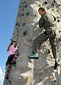 US Navy 090403-N-9860Y-003 Lt. Cmdr. Brian Danielson, assigned to Electronic Attack Squadron (VAQ) 129, gives his daughter pointers as she attempts to climb the rock wall during Northwest Outdoor Adventure Day.jpg