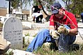 US Navy 090415-N-4750W-047 Navy chaplain Lt. Carl Muehler removes weeds around a tombstone in a local cemetery as part of a community relations project during a routine port visit.jpg