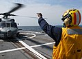 US Navy 090504-N-3215T-042 Boatswain's Mate 2nd Class Rodney Evans from Detroit, a landing signalman aboard the guided missile cruiser USS Cowpens (CG 63), signals to an SH-60B helicopter from Light Helicopte.jpg