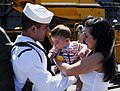 US Navy 090629-N-9610C-106 Hull Maintenance Technician 3rd Class Joel Dennett, left, from Monroe, Wash., meets his four-month old son and wife after the Nimitz-class aircraft carrier USS John C. Stennis (CVN 74) pulls into Ever.jpg