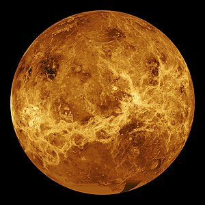 A false colour image of Venus: ribbons of lighter colour stretch haphazardly across the surface. Plainer areas of more even colouration lie between.