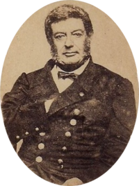 Photographic portrait of a dark-haired man with sideburns, dressed in a double-breasted military tunic with his right hand tucked under the lapel of his jacket