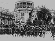 black & white photograph of Marines in a formation marching through a French street with French buildings in the background, decorated with the flags of allied nations