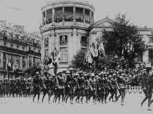 black & white photograph of Marines in a formation marching through a street with French buildings in the background, decorated with the flags of allied nations