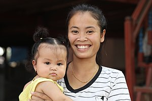 Young mother smiling while holding her baby in Laos.jpg