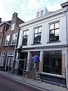 foto van Pand met verdieping onder met rode hollandse pannen gedekt zadeldak tegen topgevel en met schild