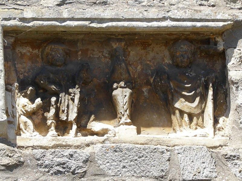 Détail du retable sculpté surmontant la porte latérale comblée de l'église Saint-Brice d'Autreville dans le département des Vosges en France.