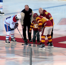 Two hockey players lean forward, facing each other, as three people standing on a carpet have each just dropped a puck to the ice.