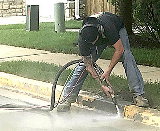Abrasive blasting - Bead blasting paint from a concrete curb. Mixing particles with water substantially reduces dust.